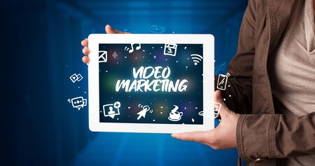 Young business person working on tablet and shows the inscription: VIDEO MARKETING Stockfoto