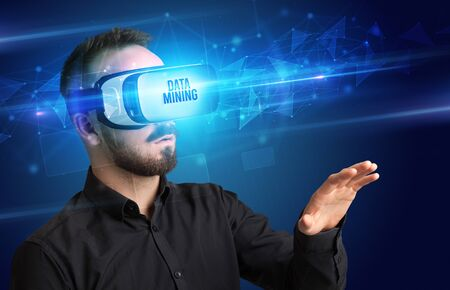 Businessman looking through Virtual Reality glasses with DATA MINING inscription, cyber security concept