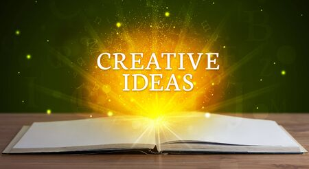 CREATIVE IDEAS inscription coming out from an open book, educational concept Stock fotó