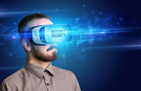 Businessman looking through Virtual Reality glasses with INTERNET SECURITY inscription, cyber security concept