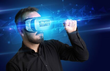 Businessman looking through Virtual Reality glasses with NETWORK SECURITY inscription, cyber security concept