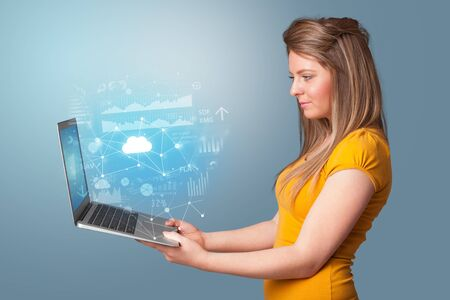 Woman holding laptop projecting cloud based system symbols and informations Stock Photo