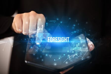 Businessman holding a foldable smartphone with FORESIGHT inscription, business concept