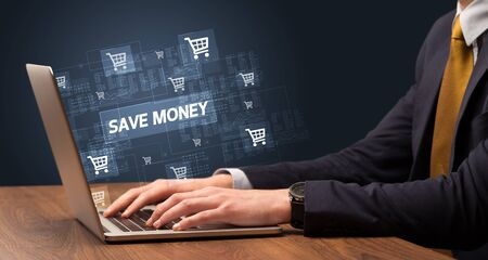 Businessman working on laptop with SAVE MONEY inscription, online shopping concept