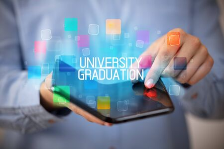 Young man holding a foldable smartphone with UNIVERSITY GRADUATION inscription, educational concept Imagens