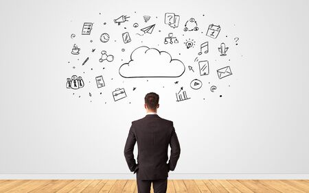 Young businessman in doubt looking to a wall with cloud technology concept