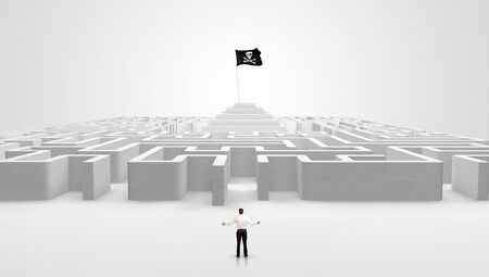 Man standing in front of a big round maze with pirate flag in the center