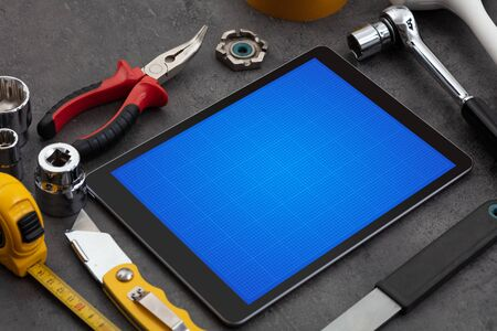 Household tools and tablet with grid screen concept 版權商用圖片