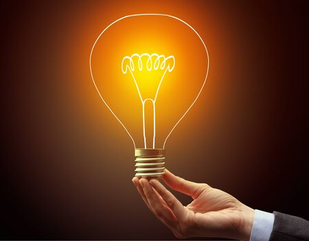 Hand holding light bulb on dark background, new idea concept