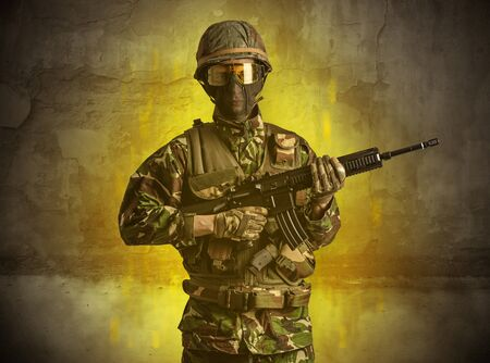 Hazard, menace soldier in a ruined crumbly building with arms on his hand Stock Photo