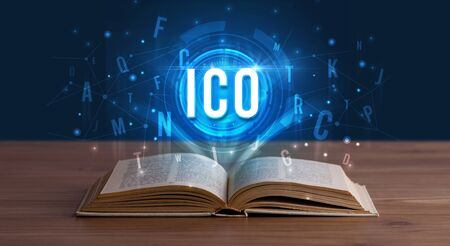 ICO inscription coming out from an open book, digital technology concept