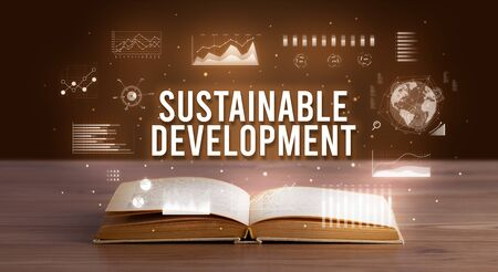 SUSTAINABLE DEVELOPMENT inscription coming out from an open book, creative business concept