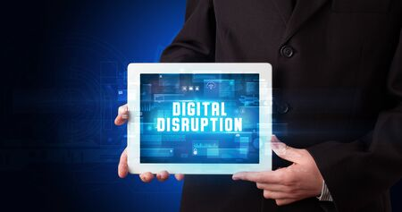 Young business person working on tablet and shows the digital sign: DIGITAL DISRUPTION