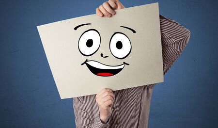 Young student holding a paper with laughing emoticon in front of his face