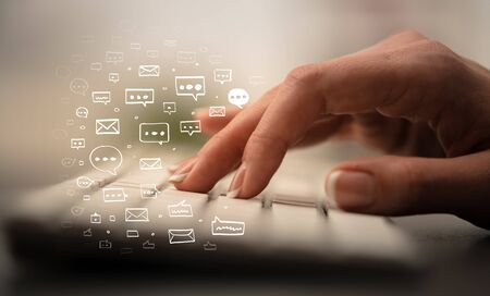 Business woman hand typing on keyboard with chat icons around