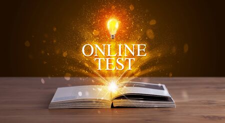 ONLINE TEST inscription coming out from an open book, educational concept 写真素材