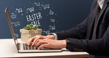 Uomo d'affari che lavora al computer portatile con iscrizione VENDITA DI PASQUA, concetto di shopping online
