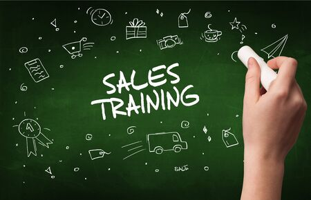Hand drawing  SALES TRAINING inscription with white chalk on blackboard, online shopping concept