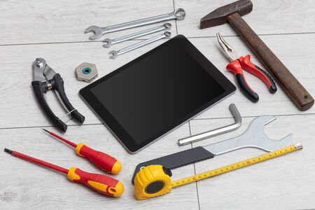 Tablet with empty screen and construction tools around  Stock Photo