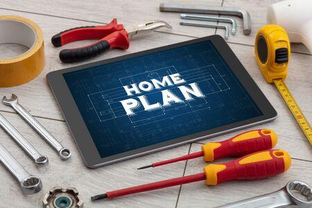 Tableta y herramientas con casa en concepto de construcción