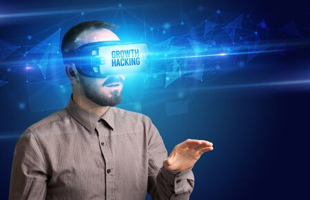 Businessman looking through Virtual Reality glasses with GROWTH HACKING inscription, cyber security concept Foto de archivo