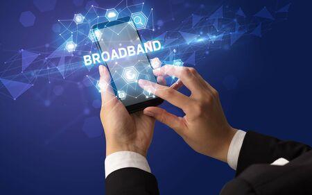 Female hand holding smartphone with BROADBAND inscription, modern technology concept Stock fotó
