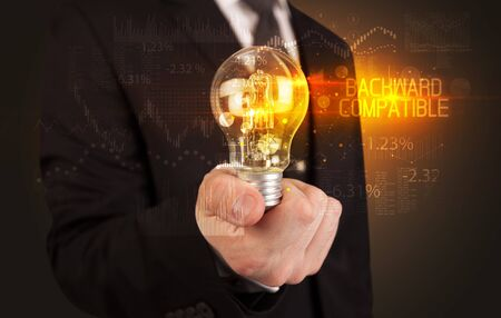 Businessman holding lightbulb with BACKWARD COMPATIBLE inscription, Business technology concept