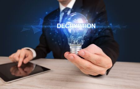 Businessman holding light bulb with DECRYPTION inscription, innovative technology concept