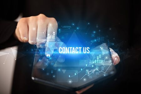 Businessman holding a foldable smartphone with CONTACT US inscription, business concept