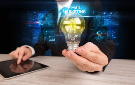 Businessman holding lightbulb with E-MAIL MARKETING inscription, online security idea concept