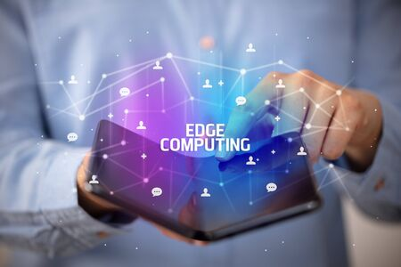 Businessman holding a foldable smartphone with EDGE COMPUTING inscription, new technology concept