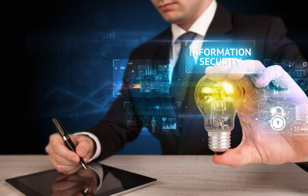 Businessman holding lightbulb with INFORMATION SECURITY inscription, online security idea concept