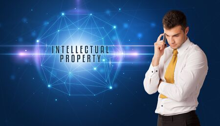 Businessman thinking about security solutions with INTELLECTUAL PROPERTY inscription 스톡 콘텐츠