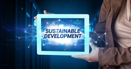 Young business person working on tablet and shows the inscription: SUSTAINABLE DEVELOPMENT Stock Photo