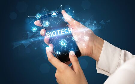 Female hand holding smartphone with BIOTECH inscription, modern technology concept Stock Photo