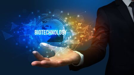 Elegant hand holding BIOTECHNOLOGY inscription, digital technology concept