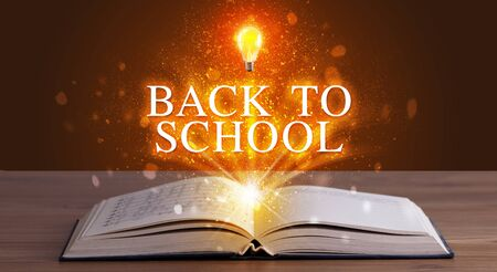 BACK TO SCHOOL inscription coming out from an open book, educational concept