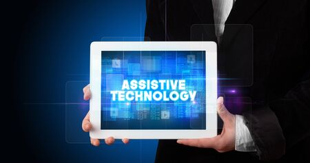 Young business person working on tablet and shows the inscription: ASSISTIVE TECHNOLOGY Stock Photo