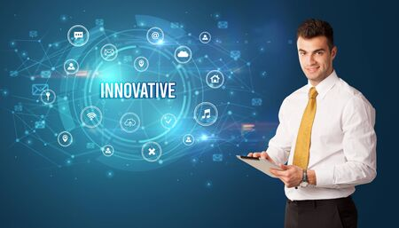 Businessman thinking in front of technology related icons and INNOVATIVE inscription, modern technology concept