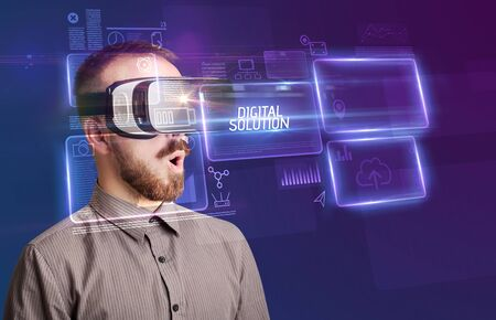 Businessman looking through Virtual Reality glasses with DIGITAL SOLUTION inscription, new technology concept