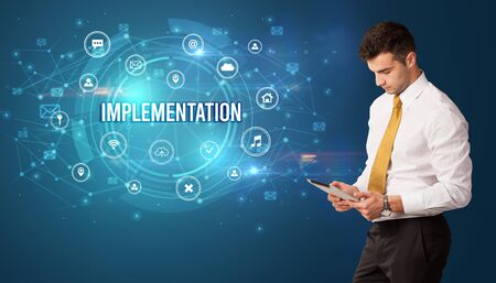 Businessman thinking in front of technology related icons and IMPLEMENTATION inscription, modern technology concept