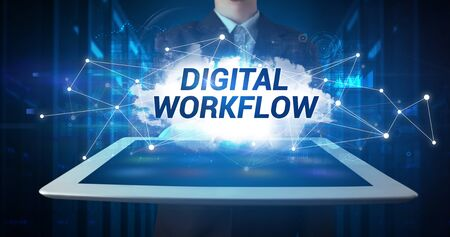 Young business person working on tablet and shows the inscription: DIGITAL WORKFLOW Stock Photo