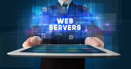 Young business person working on tablet and shows the inscription: WEB SERVERS Stock Photo