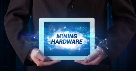 Young business person working on tablet and shows the inscription: MINING HARDWARE