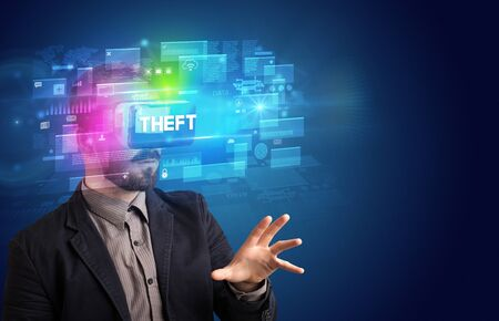 Businessman looking through Virtual Reality glasses with THEFT inscription, innovative security concept