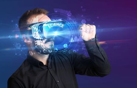 Businessman looking through Virtual Reality glasses with SCIENCE inscription, innovative technology concept
