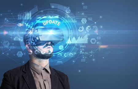 Businessman looking through Virtual Reality glasses with UPDATE inscription, innovative technology concept