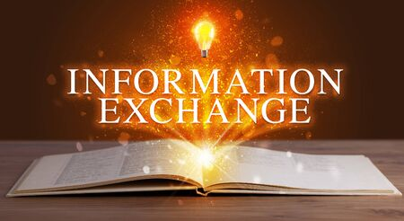 INFORMATION EXCHANGE inscription coming out from an open book, educational concept 版權商用圖片