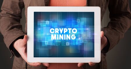 Young business person working on tablet and shows the inscription: CRYPTO MINING Stock Photo