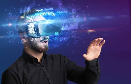 Businessman looking through Virtual Reality glasses with FINTECH inscription, innovative technology concept